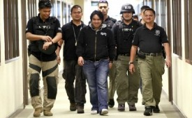 Enjoying the limelight: Benhur Luy escorted by DOJ officers