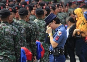 A policewoman wipes her tears
