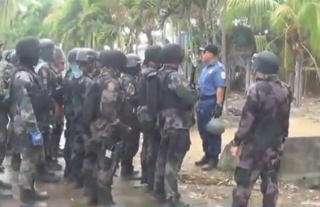 Heavily-armed Philippine Police officers regroup after rallying farmers are forcibly dispersed in Kidapawan.