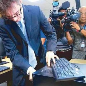 Cameras focus on Marlon Garcia of Smartmatic as he fiddles around with COMELEC equipment.