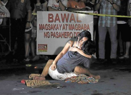 Photo of slain suspected drug pusher being held by weeping partner.