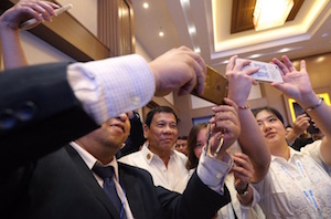 ASEAN Business & Investment Summit participants scramble to take selfies with Duterte in Laos.